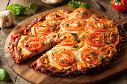Blumenkohlpizza auf Brett geschnitten Tomaten